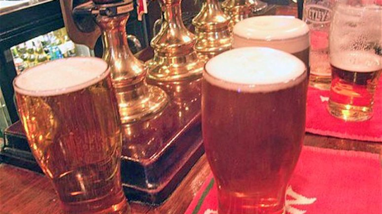A50W49 Pints of beer on the bar London pub interior England